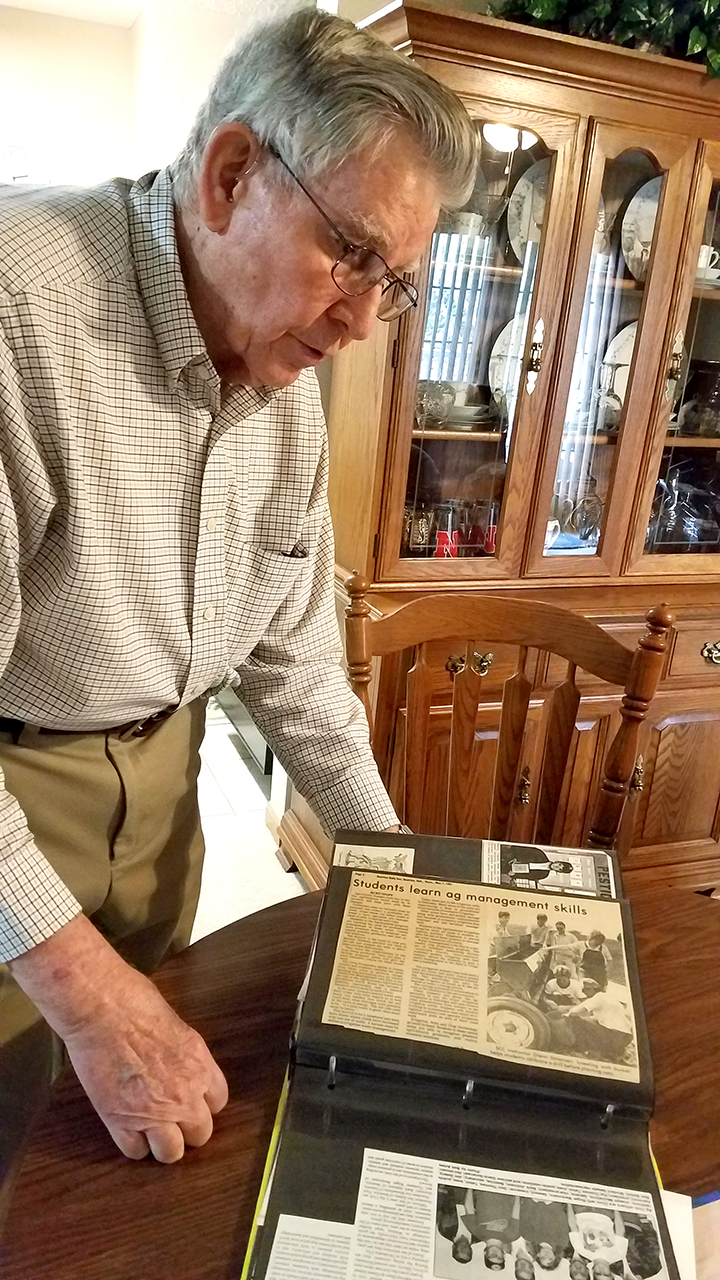 Glen Sorensen, above, looks through a scrapbook of articles from his time with the college.